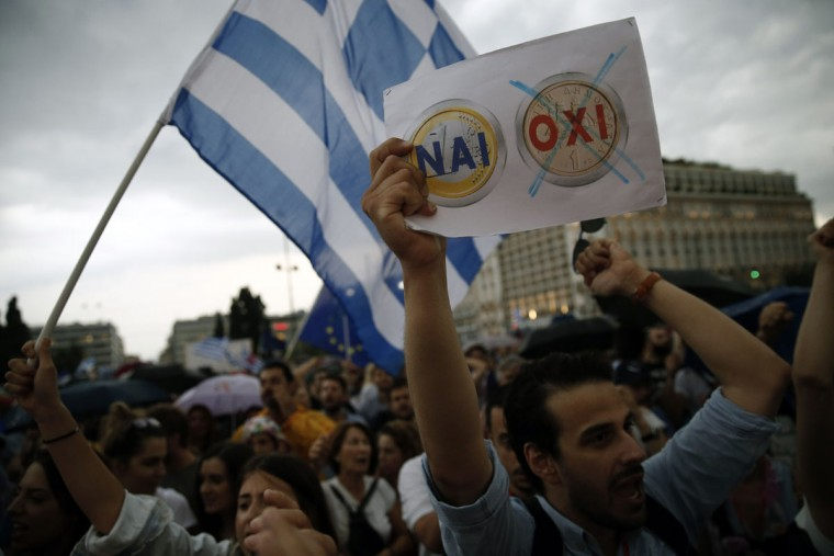 A demonstrator holds a placard depicting Yes to euro, No to drachma during a rally organized by supporters of the YES vote to the upcoming referendum in Athens, Tuesday, June 30, 2015. (AP Photo/Daniel Ochoa de Olza)