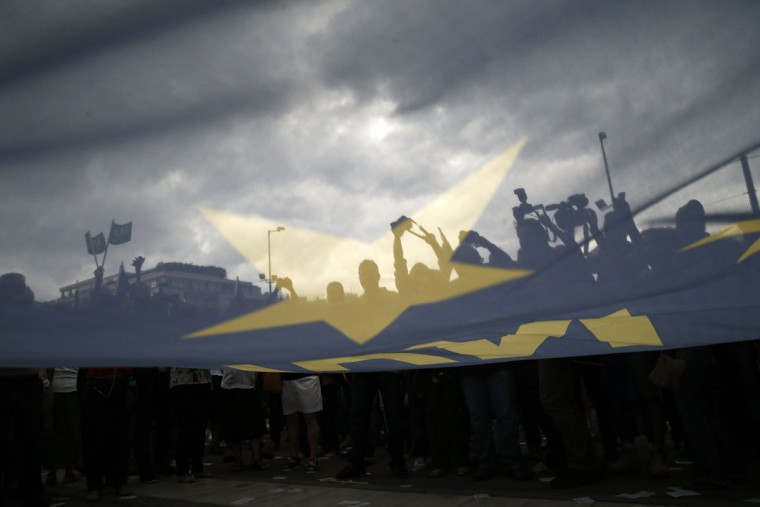 Demonstrators hold a European Union flag during a rally organized by supporters of the YES vote for the upcoming referendum in Athens, Tuesday, June 30, 2015. (AP Photo/Daniel Ochoa de Olza)