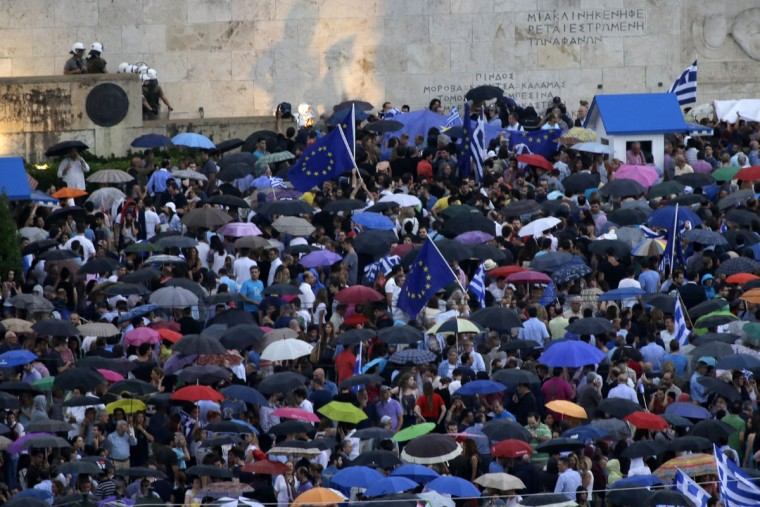 Demonstrators gather under the rain during a rally organized by supporters of the YES vote to the upcoming referendum, at Syntagma Square in Athens, Tuesday, June 30, 2015. (AP Photo/Thanassis Stavrakis)