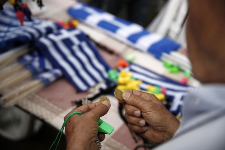 A man holds coins as he prepares to buy Greek flags during a rally organized by supporters of the YES vote to the upcoming referendum in Athens, Tuesday, June 30, 2015. (AP Photo/Daniel Ochoa de Olza)