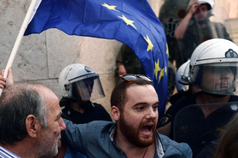 Pro-Euro protesters argue with riot police, preventing them to go up towards the parliament building in Athens on June 30, 2015. (LOUISA GOULIAMAKI/AFP/Getty Images)