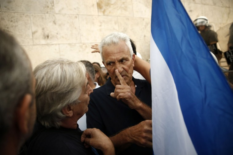 A demonstrator gestures to a man as he holds Greek flag during a rally organized by supporters of the YES vote to the upcoming referendum in Athens, Tuesday, June 30, 2015. (AP Photo/Daniel Ochoa de Olza)