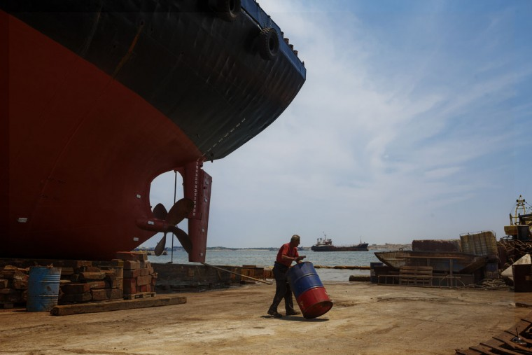 A worker pushes a drum at the Perama's Shipyards near Athens, Tuesday, June 30, 2015. (AP Photo/Daniel Ochoa de Olza)