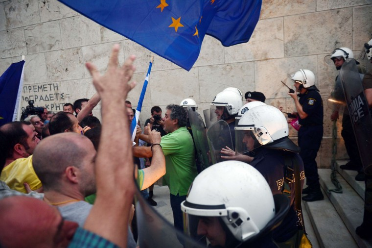 Pro-Euro protesters argue with riot police, preventing them to go up towards the parliament building in Athens on June 30, 2015. Thousands of people rallied in Athens Tuesday in support of a bailout deal with international creditors which has been rejected by Prime Minister Alexis Tsipras, leaving Greece on the brink of default. (LOUISA GOULIAMAKI/AFP/Getty Images)