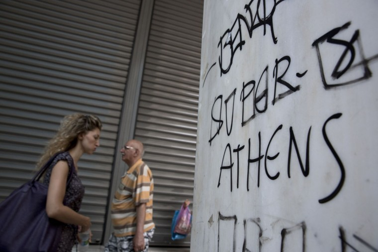 People walk past the shutters of a closed bank in central Athens on Tuesday, June 30, 2015. (AP Photo/Petros Giannakouris)