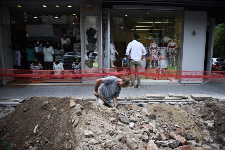 A construction worker digs a sidewalk as a man looks at the front store of a shop in the northern Greek port city of Thessaloniki, Tuesday, June 30, 2015. (AP Photo/Giannis Papanikos)