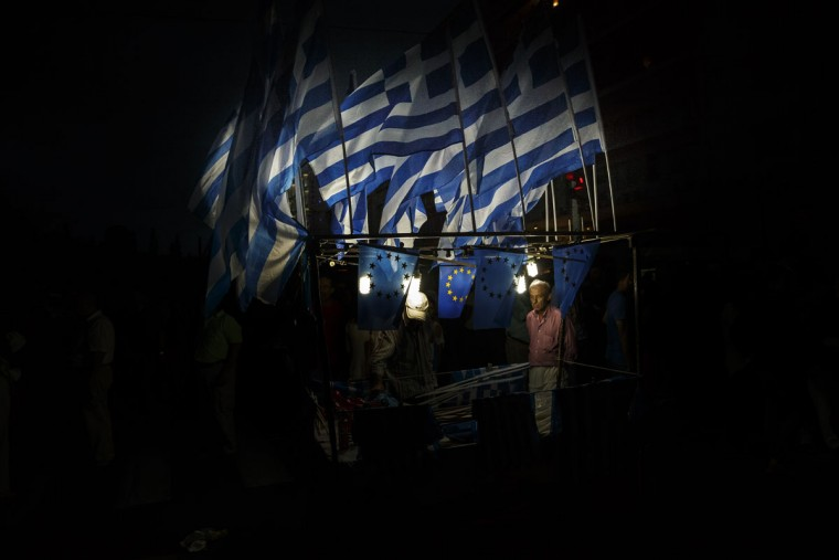 A man sells Greek and European Union flags during a rally organized by supporters of the YES vote for the upcoming referendum in front of the Greek Parliament in Athens, Tuesday, June 30, 2015. (AP Photo/Daniel Ochoa de Olza)
