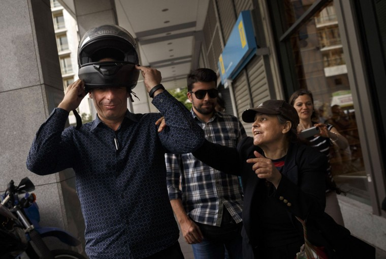 Greece's Finance Minister Yanis Varoufakis, left, is greeted by a woman as he leaves from his office in Athens, Tuesday, June 30, 2015. (AP Photo/Daniel Ochoa de Olza)
