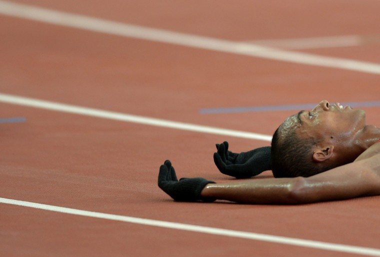 Agus Prayogo of Indonesia falls on the track after finishing in second place during the men's 5000m final athletics event at the 28th Southeast Asian Games (SEA Games) in Singapore on June 9, 2015. (MANAN VATSYAYANA/AFP/Getty Images)