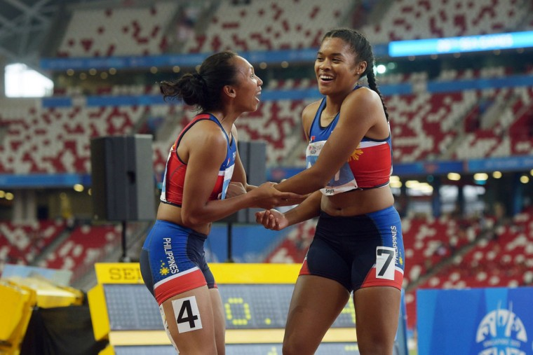 Kayla Anise Richardson, right, and Princess Joy Griffey, left, of the Philippines, celebrate Richardson's win in the Women's 100m Final at the SEA Games in Singapore, Tuesday, June 9, 2015. (AP Photo/Joseph Nair)
