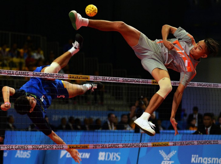 Muhammad A'fif of Singapore jumps for the ball against Pornchai Kaokaew of Thailand during the men's team sepaktakraw preliminary round match at the 28th Southeast Asian Games (SEA Games) in Singapore on June 8, 2015. (MOHD FYROL/AFP/Getty Images)