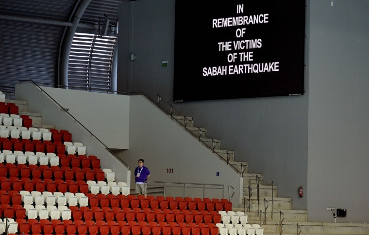 A volunteer pauses for a minute's silence prior to the start of swimming events during the 28th Southeast Asian Games (SEA Games) in Singapore on June 8, 2015. Athletes, officials and fans at Singapore's SEA Games marked a sombre minute's silence, for the six schoolchildren and two adults killed in an earthquake on Malaysia's Mount Kinabalu. (MANAN VATSYAYANA/AFP/Getty Images)