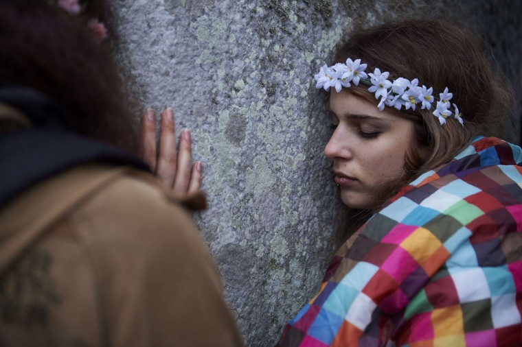 A reveller rests her head on a megalith as she and others celebrate the pagan festival of Summer Solstice at Stonehenge in Wiltshire, southern England on June 21, 2015. The festival, which dates back thousands of years, celebrates the longest day of the year when the sun is at its maximum elevation. Modern druids and people gather at the landmark Stonehenge every year to see the sun rise on the first morning of summer. (NIKLAS HALLE'N/AFP/Getty Images)
