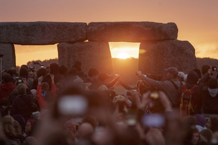 The sun rises as thousands of revellers gathered at the ancient stone circle Stonehenge to celebrate the Summer Solstice, the longest day of the year, near Salisbury, England, Sunday, June 21, 2015. (AP Photo/Tim Ireland)