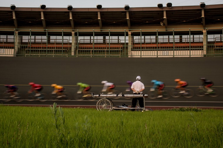 A safety officer stands next to a stretcher as riders pass by during a Keirin race at the Kawasaki Velodrome on July 11, 2015 in Kawasaki, Japan. (Photo by Chris McGrath/Getty Images)