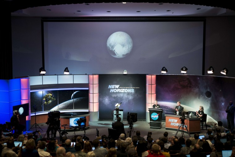 People look at an early image of Pluto taken by NASA's New Horizons probe as the craft makes its closest fly-by of the dwarf planet at the Johns Hopkins University Applied Physics Laboratory July 14, 2015 in Laurel (AFP PHOTO/BRENDAN SMIALOWSKIBRENDAN SMIALOWSKI/AFP/Getty Images)