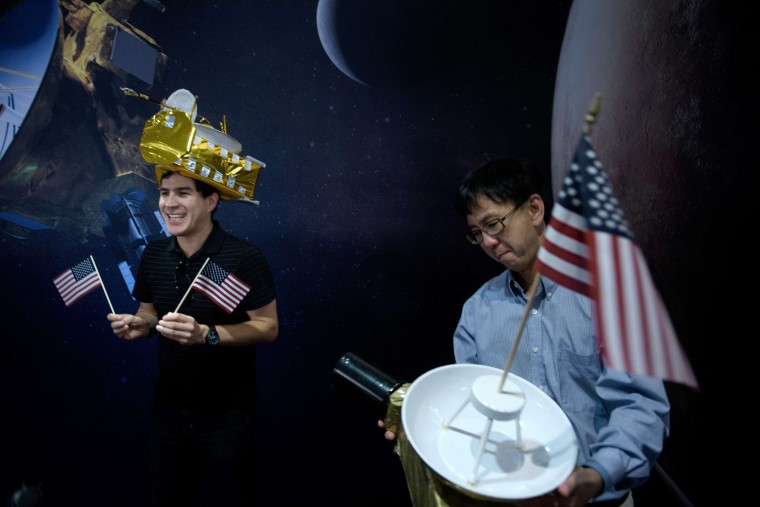 Carlos Nieto (L) and Nam Phamdo pose with New Horizons probe hats at the Johns Hopkins University Applied Physics Laboratory July 14, 2015 in Laurel, Maryland. The unmanned NASA spacecraft whizzed by Pluto on July 14, making its closest approach in the climax of a decade-long journey to explore the dwarf planet for the first time, the US space agency said. (AFP PHOTO/BRENDAN SMIALOWSKIBRENDAN SMIALOWSKI/AFP/Getty Images)