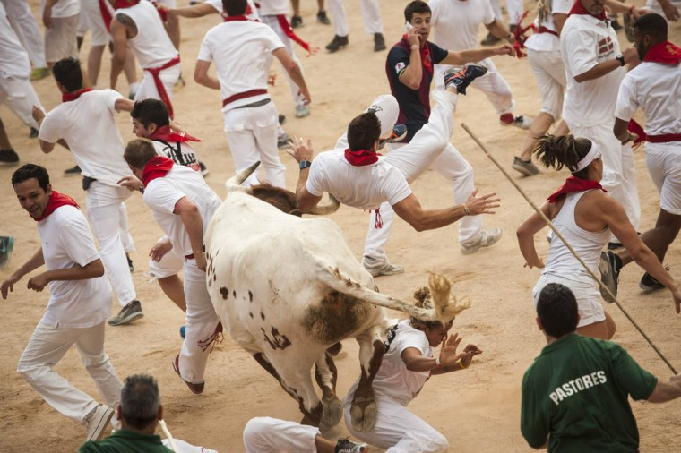A runner is knocked by a steer during the second running of the bulls at the San Fermin Festival, in Pamplona, Spain, Wednesday, July 8, 2015. Revelers from around the world arrive to Pamplona every year to take part in some of the eight days of the running of the bulls. (Alvaro Barrientos/AP photo)