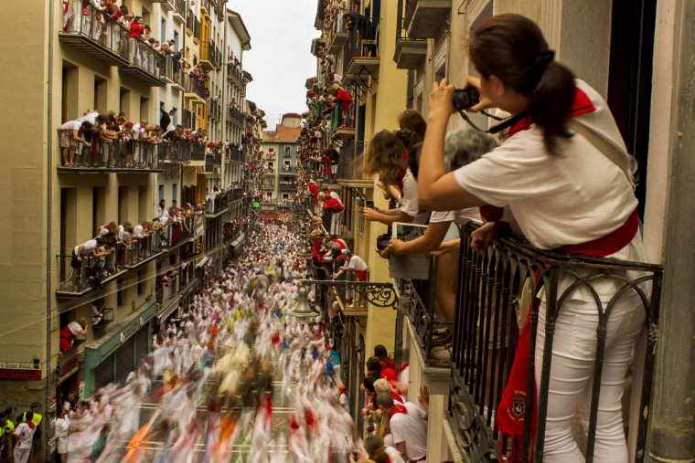People watch as El Tajo y La Reina fighting bulls and revelers run during the running of the bulls, at the San Fermin festival. (Andres Kudacki/AP photo)