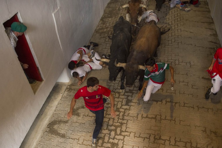 "Runners fall beside two ''El Tajo-La Reina"" fighting bulls during the second running of the bulls at the San Fermin Festival, in Pamplona, Spain, Wednesday, July 8, 2015. (Alvaro Barrientos/AP photo)"