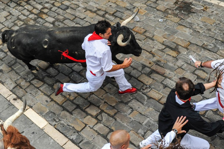 Revelers run with the Tajo and the Reina's fighting bulls entering Estafeta street during the third day of the San Fermin Running of the Bulls festival. (David Ramos/Getty Images)