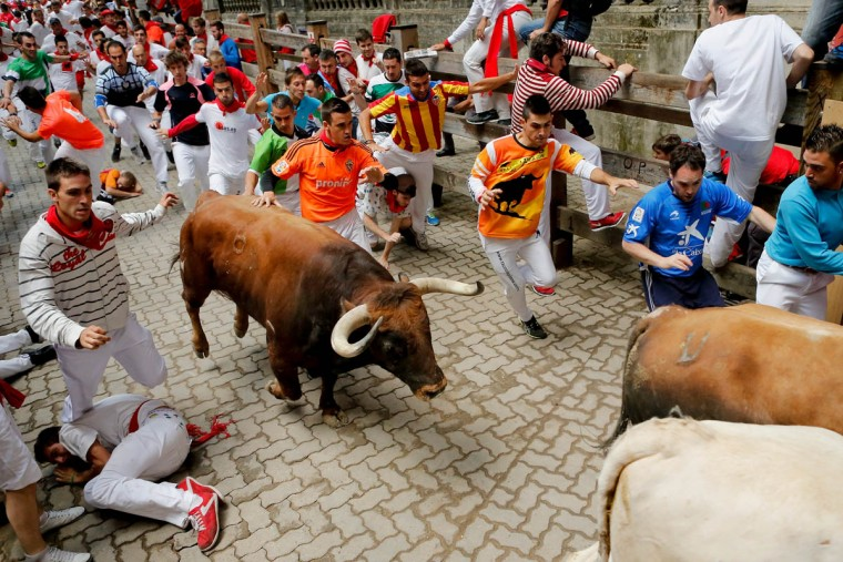 Revelers run with the Tajo and the Reina's fighting bulls entering the bullring during the third day of the San Fermin Running Of The Bulls festival in Pamplona, Spain. (Pablo Blazquez Dominguez/Getty Images)