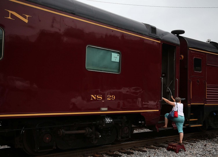 ROANOKE, VA - JULY 03: A women climbs into a passanger car on the recently restored former Norfolk and Western Railway J class steam locomotive 611 passes by during an excursion July 3, 2015 in Roanoke, Virginia. The 611 was originally retired and replaced by diesel locomotives in 1959 and now is running excursions on a limited schedule. (Photo by Mark Wilson/Getty Images)