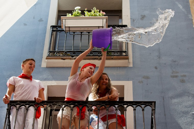 Revellers throw a bucket of water from a balcony to the crowd during the opening day or 'Chupinazo' of the San Fermin Running of the Bulls fiesta on July 6, 2015 in Pamplona, Spain. (Photo by Pablo Blazquez Dominguez/Getty Images)