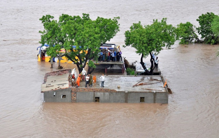 This handout photograph released by The Indian Ministry of Defence on June 25, 2015, shows Indian villagers standing on a building awaiting rescue by authorities as floodwaters rise in Amreli District, some 200kms south-west of Ahmedabad in the western state of Gujarat on June 24, 2015. Heavy rains from a weather depression in the Arabian Sea have moved across the state as the annual monsoon makes its way across the Indian sub-continent. (AFP Photo/P /mod )