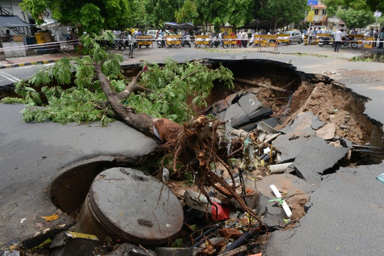 Indian onlookers stand near a section of road damaged by heavy rains in Ahmedabad on June 25, 2015. Some 45 people have been killed in heavy rains in parts of the state of Gujarat. (AFP Photo/Sam Panthaky)