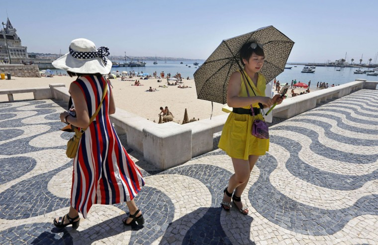 A tourist uses an umbrella to protect from the sun as she goes for a walk by Cascais' beach on the outskirts of Lisbon on June 29, 2015. Temperatures soared above 40 degrees (104 degrees Fahrenheit) across Spain and Portugal on June 29, 2015, prompting heat alerts, raising the risk of wildfires and drawing crowds to beaches and fountains. (AFP Photo/Jose Ribeirojose manuel ribeiro)
