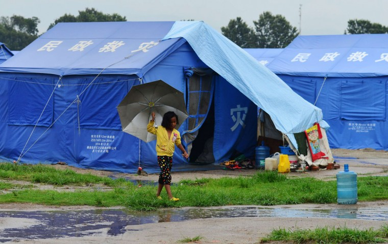 A Nepalese child walks in the rain through a relief camp for survivors of the Nepal earthquake in Kathmandu on July 1, 2015, following twin earthquakes which struck the Himalayan nation in April and May 2015. The World Bank announced in June 2015 that it will provide up to USD 500 million for reconstruction in quake-devastated Nepal. The twin quakes that struck in April and May killed more than 8,800 people, destroyed nearly half a million houses and damaged another 280,000, leaving thousands in need of food, clean water and shelter. (PRAKASH MATHEMA/AFP/Getty Images)