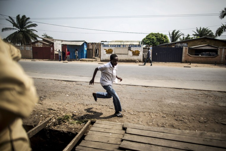 A boy runs for cover during a heavy burst of fire in the restive Cibitoke neighborhood in Bujumbura during the celebrations of the Country 53rd Independence Anniversary on July 1st, 2015. Six people including a policeman were killed in gun battles on July 1 in the latest violence in Burundi, as it awaits results from elections boycotted by the opposition and condemned internationally. Elsewhere in the capital, military parades were held to mark the country's independence day. (MARCO LONGARI/AFP/Getty Images)