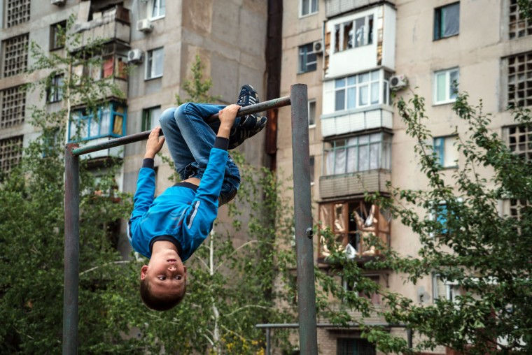 A boy, a resident of the large industrial town of Horlivka in the Donetsk region, adjacent to the front line, plays on a horizontal bar on June 30, 2015. (ANDREY BORODULIN/AFP/Getty Images)