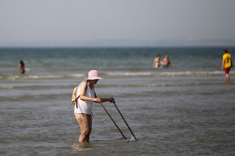 An elderly woman walks in the sea at the French northwestern city of Deauville on July 1, 2015, as a blistering heatwave sweeps through Europe with temperatures pushing 40 degrees Celsius. (CHARLY TRIBALLEAU/AFP/Getty Images)