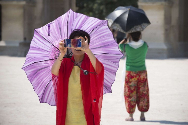 Women carrying parasols to protect themselves from the sun take pictures on July 1, 2015 in Paris. (JOEL SAGET/AFP/Getty Images)