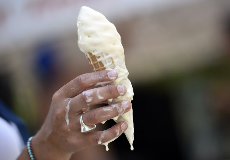 A woman eats a melting ice cream on July 2, 2015 in Paris. (AFP Photo/Loic Venance)