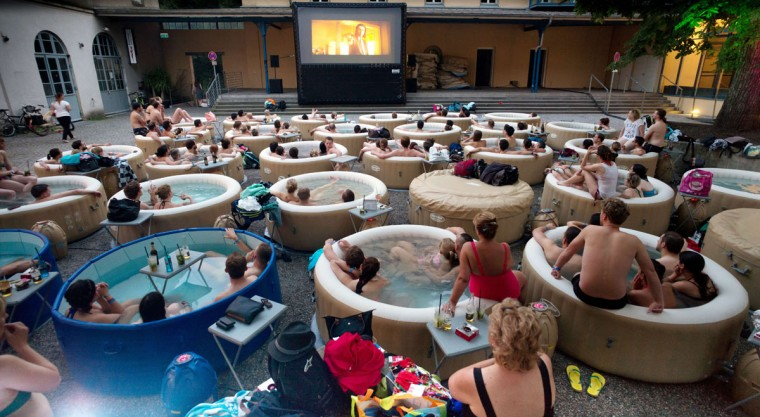 Spectators sitting in whirlpools together watch the film 'Pulp Fiction' shown on a large screen on Prater Island in Munich on July 3, 2015. (AFP Photo/Dpa / )