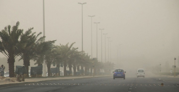 Cars drive along the street in Kuwait City during a heavy dust storm on July 7, 2015. (AFP Photo/Yasser Al-zayyat)