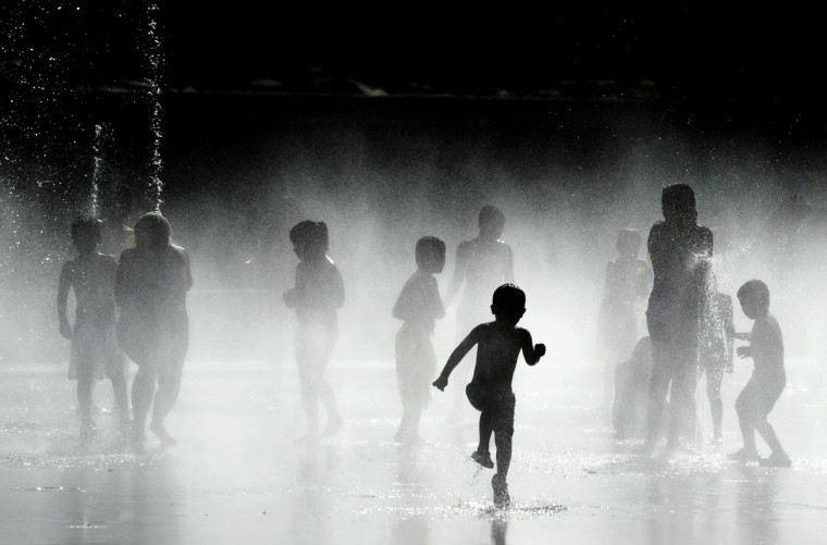 Children play with the water of fountains on the banks of the Manzanares river in Madrid on July 7, 2015. In Spain started on July 1, 2015 a new heatwave which will last for at least nine days and extend to the rest of Europe. The heatwave, the second of the summer, will affect almost all of Spain. (AFP Photo/P / )