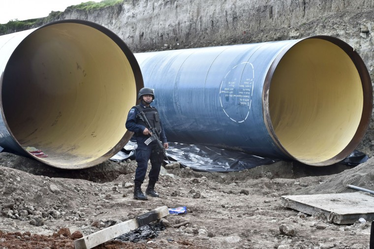 "A policeman stands guard near a pipeline under construction in the surroundings of the Altiplano prison in Almoloya de Juarez, Mexico on July 12, 2015. Mexican drug lord Joaquin ""El Chapo"" Guzman has escaped from a maximum-security prison, the government said Sunday, his second jail break in 14 years. The kingpin was last seen in the shower area of the Altiplano prison in central Mexico late Saturday before disappearing. ""The escape of Guzman was confirmed"", the National Security Commission said in a statement. (Yuri Cortez/AFP/Getty Images)"