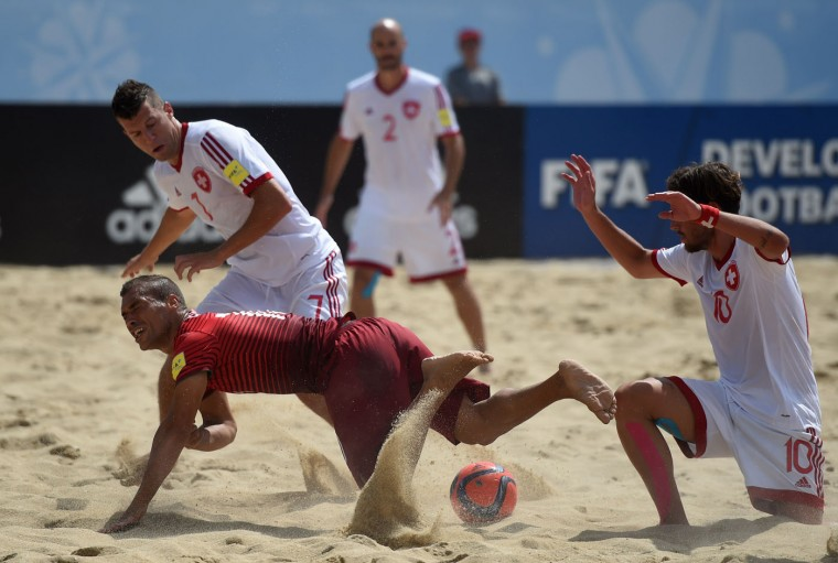 Portugal's wing Belchior (DownL) vies with Switzerland's wing Sandro Spaccarotella (L) and wing Philipp Borer (R) during the FIFA Beach Soccer World Cup football match Portugal vs Switzerland in Espinho on July 16, 2015. (Francisco Leong/AFP/Getty Images)