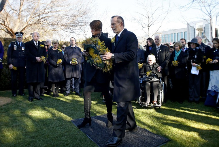Australia's Prime Minister Tony Abbott (centre R) and his wife Margaret prepare to lay a wreath for the Australian victims of Malaysia Airlines flight MH17 at a ceremony unveiling a memorial on the first anniversary of the plane's downing, outside Parliament House in Canberra on July 17, 2015. All 298 passengers and crew on board the Malaysia Airlines flight MH17 Boeing 777 were killed, the majority of them Dutch, but with 38 Australian citizens and residents among them, when the plane was shot down over Ukraine. (AFP Photo/Pool / )