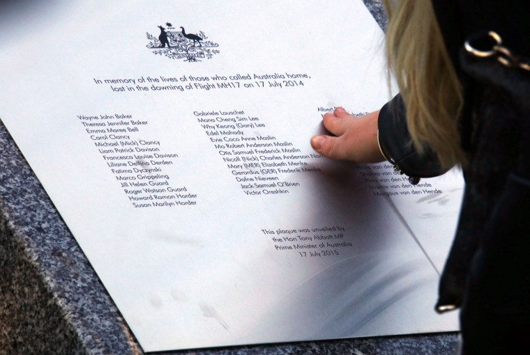 A relative of an Australian victim of Malaysia Airlines flight MH17 touches a memorial that was unveiled outside Parliament House to mark the first anniversary of the plane's downing, in Canberra on July 17, 2015. All 298 passengers and crew on board the Malaysia Airlines flight MH17 Boeing 777 were killed, the majority of them Dutch, but with 38 Australian citizens and residents among them, when the plane was shot down over Ukraine. (AFP Photo/Pool / )