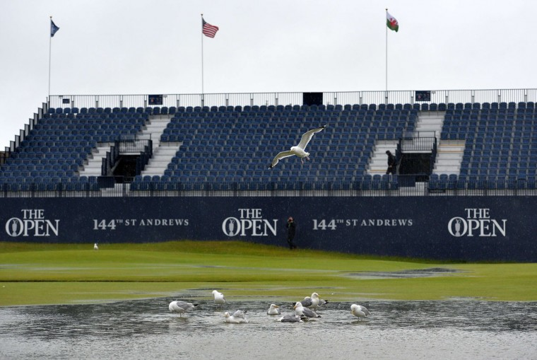 Gulls enjoy the water-logged 1st fairway as standing water is seen on the 1st green behind after heavy rain make the course unplayable early on the second day of the 2015 British Open Golf Championship on The Old Course at St Andrews in Scotland, on July 17, 2015. By 8:00 p.m. large puddles had formed on the Old Course's fairways and greens as the deluge continued and director of greenkeeping Gordon Moir said that no time could yet be set for play to resume. (AFP Photo/Glyn Kirk)