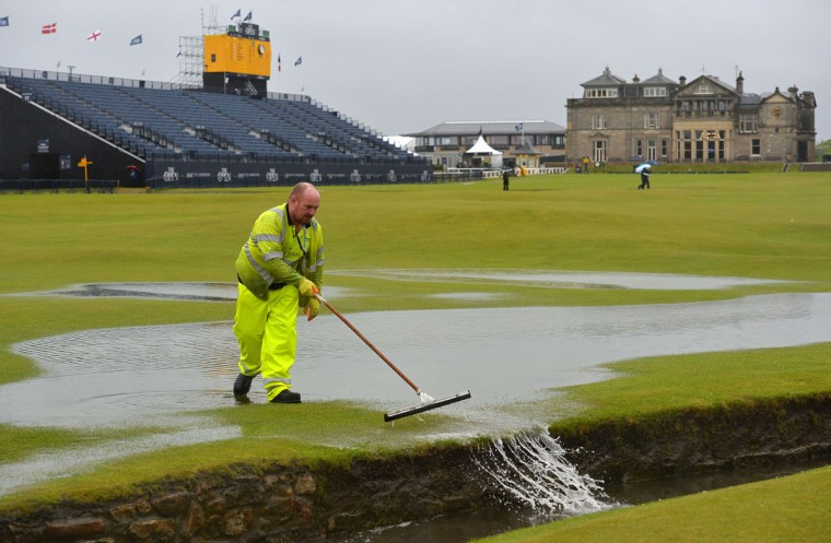A groundsman sweeps water into the Swilcan Burn from the 1st fairway, after heavy rain make the course unplayable early on the second day of the 2015 British Open Golf Championship on The Old Course at St Andrews in Scotland, on July 17, 2015. By 8:00 p.m. large puddles had formed on the Old Course's fairways and greens as the deluge continued and director of greenkeeping Gordon Moir said that no time could yet be set for play to resume. (AFP Photo/Glyn Kirk)