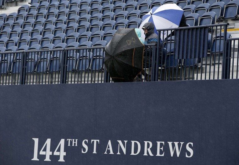 Spectators shelter under umbrellas as heavy rain make the course unplayable early on the second day of the 2015 British Open Golf Championship on The Old Course at St Andrews in Scotland, on July 17, 2015. By 8:00 p.m. (0700GMT) large puddles had formed on the Old Course's fairways and greens as the deluge continued and director of greenkeeping Gordon Moir said that no time could yet be set for play to resume. (AFP Photo/Adrian Dennis)