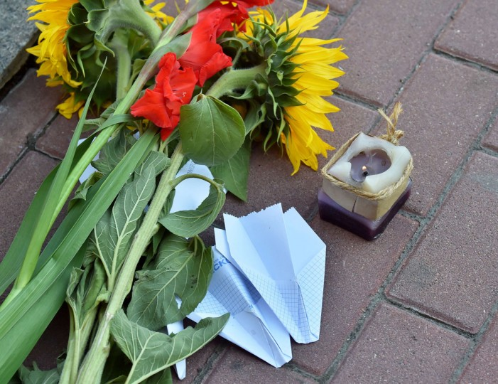 Flowers, a candle and paper aiplanes lie on the pavement in front of the Dutch embassy in Kiev on July 17, 2015 in memory of the people who died in the crash of Malaysian Airlines flight MH17. All 298 passengers and crew -- the majority Dutch -- died on July 17 last year when the Malaysia Airlines Boeing 777, on a flight between Amsterdam and Kuala Lumpur, was shot down over rebel-held east Ukraine during heavy fighting between Ukrainian forces and pro-Russian separatists. (AFP Photo/P / )
