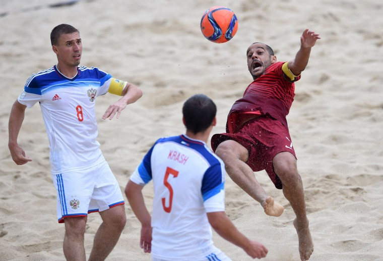 Portugal's wing Madjer (R) vies with Russia's defender Ilya Leonov (L) and defender Yury Krasheninnikov during the FIFA Beach Soccer World Cup football match Portugal vs Russia in Espinho on July 18, 2015. (Francisco Leong/AFP/Getty Images)