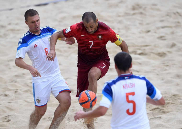 Portugal's wing Madjer (C) vies with Russia's defender Ilya Leonov (L) and defender Yury Krasheninnikov during the FIFA Beach Soccer World Cup football match Portugal vs Russia in Espinho on July 18, 2015. (Francisco Leong/AFP/Getty Images)